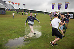 © Joel Goodman - 07973 332324 . 11/06/2016 . Manchester , UK . A reveller splashes through a water puddle at the Parklife music festival at Heaton Park in Manchester . Photo credit : Joel Goodman