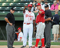 Manager Chris Truby, right center, of the Lakewood BlueClaws, and Billy McMillon, left center, of the Greenville Drive, discuss ground rules with umpires Jose Esteras, left, and Roberto Ortiz prior to a game on July 12, 2011, at Fluor Field at the West End in Greenville, South Carolina. (Tom Priddy/Four Seam Images)