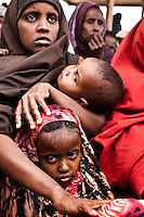 A Somali refugee woman cradles her baby after dousing her elder daughter with water to keep cool under the sweltering sun in Dagahaley refugee camp near Dadaab, Kenya.
