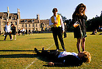 GIRL POURING BEER ONTO HALF ASLEEP STUDENT, LYING, DRUNK, OUTSIDE ON THE GRASS PLAYING FIELD IN THE MORNING AFTER THE ROYAL AGRICULTURAL COLLEGE BALL, CIRENCESTER, 1990s UK
