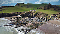 BNPS.co.uk (01202 558833)<br /> Pic: RichardDowner/TheCoastalHouse/BNPS<br /> <br /> Pictured: An aerial view of the property.<br /> <br /> An off-grid beachside 'oasis' that has no mains water or electricity is on the market for £550,000.<br /> <br /> The former coastguard cottage is the ultimate retreat for those looking to get away from the modern world - with an outside toilet, 'gravity' shower and no wi-fi.<br /> <br /> It is one of three cottages, built by Napoleonic prisoners of war, above the remote National Trust-owned Mansands Beach, between Kingswear and Brixham in Devon.<br /> <br /> The two-bedroom cottage has spectacular panoramic views of the sea and the South Devon coastline and the three properties also share access to a private cove below.