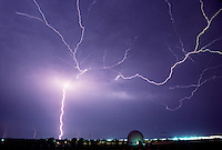 A variety of cloud-to-cloud and cloud-to-ground lightning etches a bright path across the night sky over the old Norman Doppler research radar at the National Severe Storms Laboratory in Norman Oklahoma.
