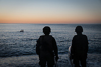 CEUTA, SPAIN ‐ MAY 19: A group of young people try to swim across the border from Morocco to Spain, bordering the beach of Tarajal while two soldiers of the Spanish army, wait for them to step on land to be returned to Morocco on May 19, 2021 in Ceuta, Spain.  After a diplomatic conflict between Spain and Morocco, thousands of migrants who have taken advantage of the little Moroccan police activity on the border to cross it mainly by swimming, which has caused a migration crisis with the entry of more than 8000 migrants from the African country. (Photo by Joan Amengual/VIEWpress )
