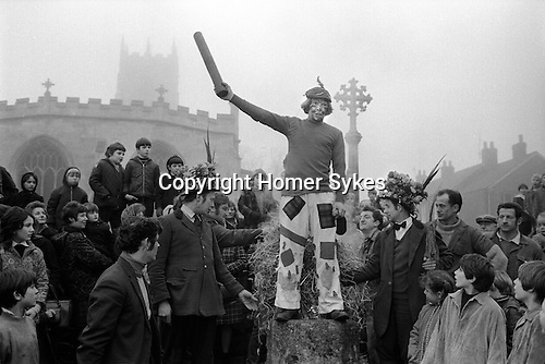 Haxey Hood Game. Haxey, Lincolnshire. Smoking the Fool. 1972.<br /> <br /> It is unclear how this rough version of rugby football began, it can only be traced with some certainty to an incident involving the first Lady de Mowbray who married John de Mowbray in 1298. One day when she was out riding her hood blew off and thirteen farm workers or 'Boggins' in the vicinity gave chase to it. When it was finally rescued by the 'fool' he was too shy to hand it over, so another Boggin (the 'Lord') gave it to her. Lady de Mowbray was so impressed with this gallantry that in her will she left a piece of land called the 'Hoodlands' to the village as long as the inhabitants promised to re-enact the event annually. Consequently, each year on the 6 January the people not only of Haxey, but also of Westwoodside and other surrounding villages, do so. There are thirteen Boggins, the lord and the chief Boggin wear hunting pink, the fool the attire of a court jester.  After much singing of traditional songs in the village pubs, after lunch, they gather at the mounting stone by the village church where the fool makes a dash away from the crowd and the Boggins give chase until he is caught. They then carry him back to the stone where he tells the crowd the legend and the rules. <br /> <br /> They then make their way with the crowd to Upper Thorpe Field on the boundary of Westwoodside and Haxey There twelve sack hoods are thrown up. These are known as children's hoods. At about four o'clock a leather hood is thrown up, and a scrum known as the 'sway' forms round it. The teams of men, push against each other trying to get the hood to their favourite pub. Usually several hours pass before the hood reaches a goal, and when it does drinks are on the house. The hood stays in the pub until the following New Year's Eve when it<br /> is redeemed by the Boggins. <br /> <br /> Chief Boggin Arthur Clark & the Fool Peter Bee about to be smoked, the Lord is played by Stan Boor.<br /> <br /> <br /> My