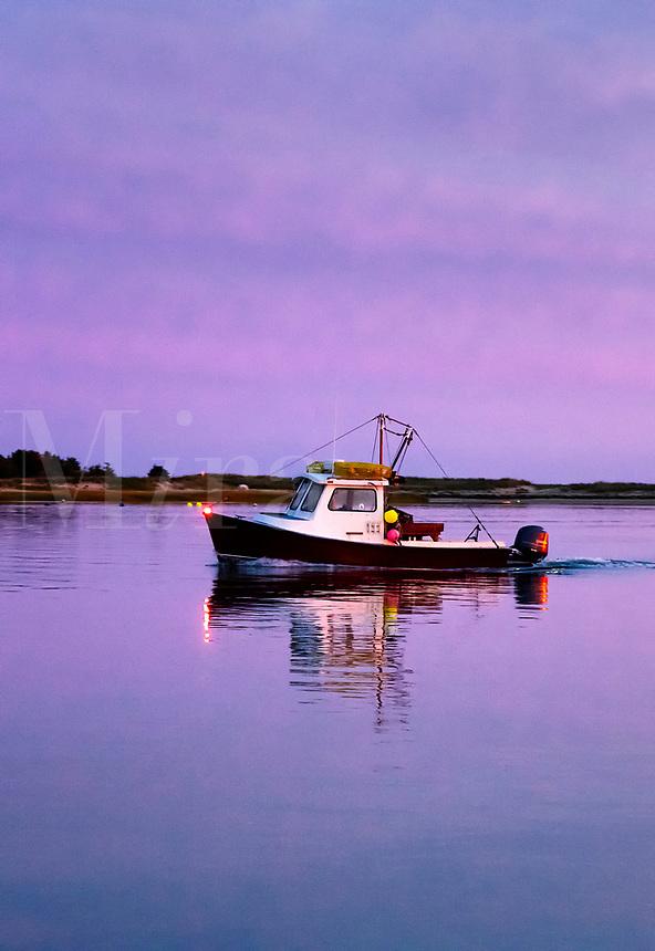 Fishing boat returns to harbor at sunset.