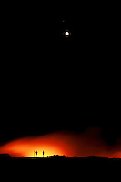 The tiny silhouettes of three volcano spectators are illuminated against fiery eruptions from dark lava fields and a full moon in the black sky.