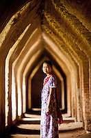 A teenage girl selling souvenirs wanders around the Maha Aung Mye Bon San Monastery, in the ancient city of Ava in Myanmar