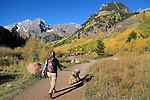 Woman walking her dog along Maroon Creek with South and North Maroon Peaks behind, near Aspen, Colorado, USA .  John offers private photo tours in Denver, Boulder and throughout Colorado. Year-round.