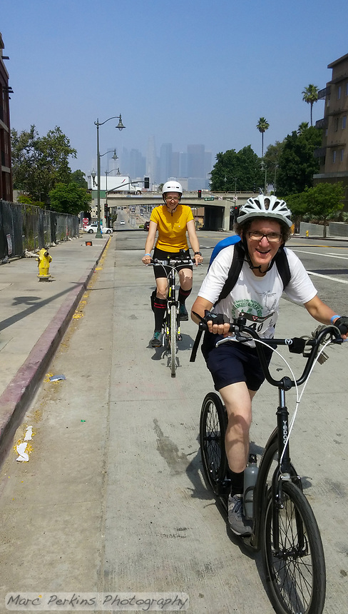 Holland kicks up the 1st street hill on his Yedoo kick scooter, with Michelle smiling close behind him.  The LA skyline and the 101 freeway bridge can be seen behind them. Taken during the 2017 (17th annual) Los Angeles River Ride.