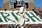 """GPUB 28/25:  Football Game Scene - Notre Dame vs. Stanford, 1964/1024.  Marching Band Drum Major inside Notre Dame Stadium while fans hold cards that spell out """"Irish"""" in the background.<br /> Photo by Bruce Harlan, University Photographer.  Image from the University of Notre Dame Archives."""