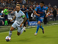 KANSAS CITY, KS - MAY 29: Johnny Russell #7 of Sporting KC dribbles up the right wing as Joe Corona #14 of Houston Dynamo FC tries to catch up to him during a game between Houston Dynamo and Sporting Kansas City at Children's Mercy Park on May 29, 2021 in Kansas City, Kansas.