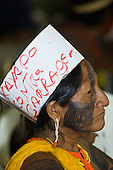 "Altamira, Brazil. ""Xingu Vivo Para Sempre"" protest meeting about the proposed Belo Monte hydroeletric dam and other dams on the Xingu river and its tributaries. Kayapo woman wearing a cardboard headband with ""Kayapo Contra Barragem"" written on it."