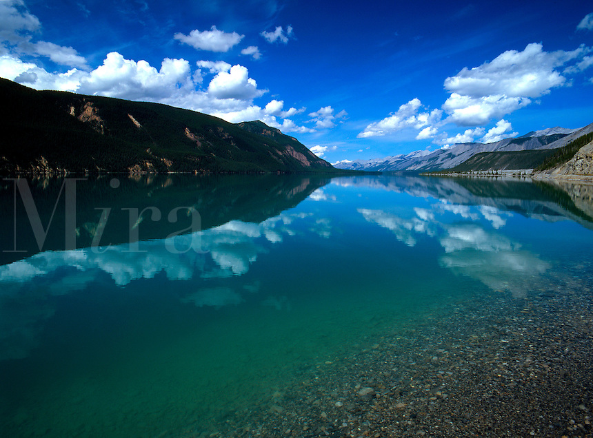 Art in Nature 9607-0127 - Muncho Lake, located along the Canada Highway in Northern British Columbia is a great lake for reflections. Here, its azure blue water reflects the white cumulus clouds of an equally azure blue sky. Northern Rocky Mountains, Brit