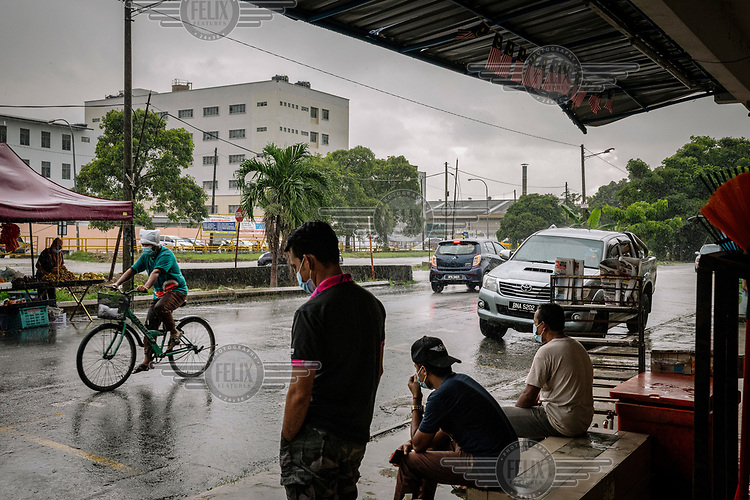 Locals and migrant workers take shelter from the rain beneath shop awnings on a street behind Kossan Rubber Industries Bhd. The company has temporarily suspended operations at one of its plants in Klang after 427 employees were infected with COVID-19.