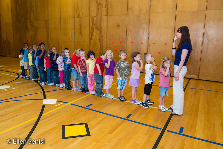 MR / Schenectady, NY. Zoller Elementary School (urban public school). Kindergarten inclusion classroom. Students line up in front of their teacher in school gym after completing physical education class. After physical activity, they need to settle down. She is focusing their attention by having them follow directions and imitate her motions. One student is not paying attention. MR: War15. ID: AM-gKw. © Ellen B. Senisi.
