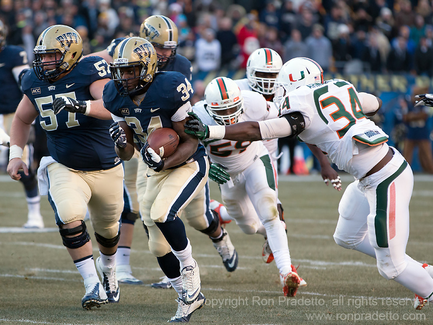 Pitt running back Isaac Bennett (34) heads to the endzone on a 45-yard touchdown run as Miami defensive back Kacy Rodgers II (22) tries to tackle him.  The Miami Hurricanes defeated the Pitt Panthers 41-31 at Heinz Field, Pittsburgh, Pennsylvania on November 29, 2013.