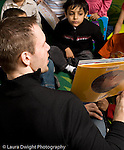 Education Preschool 3-5 year olds male teacher reading to group of children vertical