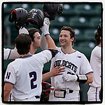 Catcher Michael Trautwein (23) of the Northwestern Wildcats is greeted after hitting a grand slam home run in the third inning of a game against the Michigan State Spartans on Friday, March 12, 2021, at Fluor Field at the West End in Greenville, South Carolina. Northwestern won, 14-2. (Tom Priddy/Four Seam Images)