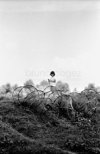 ROMANIA, Delta of Danube, Mila 23, April 2000..A child is playing alone behind fishing nets..ROUMANIE, Delta du Danube, Mila 23, Avril 2000..Un enfant joue seul derrière les casiers de peche..© Bruno Cogez