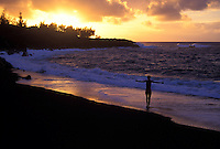 Woman standing at Kahena's black sand beach on the puna side of the Big Island
