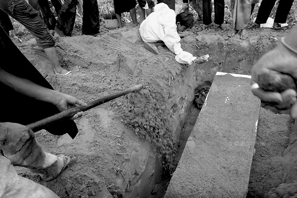 Peod takes a last photo of his mother before she is buried. <br /> <br /> On April 27, Mrs Mool Klatalay was savagely beaten by her drunken husband. The beating took place in the hovel where Mool lived in a small sea gypsy village in southern Thailand's Phang Nga province. Villagers heard her screams, but no one intervened. No one took her to hospital. She died at home 48 hours later, after losing four pints of blood through internal bleeding. She leaves two sons, aged 19 and 12, and a daughter, aged 3.