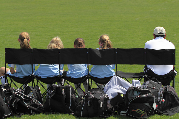 Coach and bench warmers on a girls soccer team, Denver, Colorado, USA. .  John leads private photo tours in Boulder and throughout Colorado. Year-round.