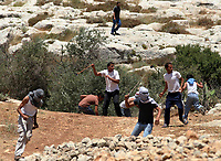 """Palestinian youth throw stones at Israeli soldiers during a demonstration against the construction of Israel's controversial separation barrier in the West Bank village of Nilin, west of Ramallah on May 25, 2008. """"photo by Iyad Jadallah"""""""