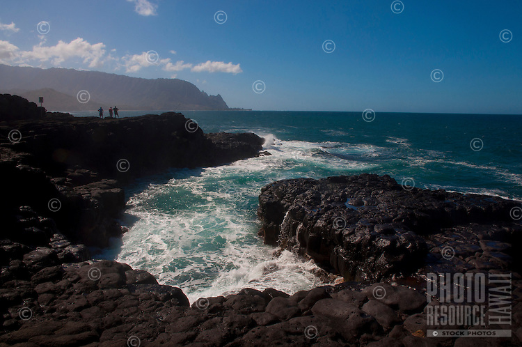 North shore winter waves crashing into black lava rocks at the Queen's Bath area in Princeville, Kauai, with Na Pali cliffs in the background.