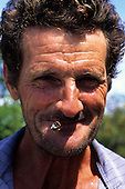 Juruena, Amazon, Brazil. Man with an unshaven weatherbeaten face smoking a home made cigarette rolled in a leaf.