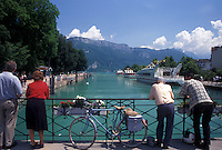 Annecy, France, Haute-Savoie, Rhone-Alpes, Europe, People looking at scenic Thiou canal and Lake Annecy (Lac d' Annecy) from bridge on the waterfront in Annecy.