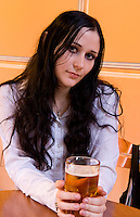 The Gothic life of teenage girl having beer at restaurant in black dress in Kiev Ukraine as alternative lifestyle