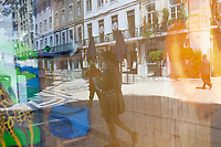 LISBON, PORTUGAL - MAY 18 :  People using protective facemasks are seen reflected on a stained glass window of a store still closed in Lisbon, on May 18, 2020. <br /> Restaurants, museums and coffee shops reopen at reduced capacity, while Lisbon eases lockdown coronavirus disease (COVID-19) outbreak.<br /> (Photo by Luis Boza/VIEWpress via Getty Images)