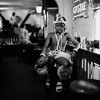 Khawulani, a boy dressed in traditional Zulu style, sits at the bar of Quenchers Pub in Kruis Street...