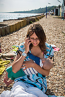 """A young woman breastfeeding her baby while sitting on a beach and talking on a mobile phone.<br /> <br /> Image from the breastfeeding collection of the """"We Do It In Public"""" documentary photography picture library project: <br />  www.breastfeedinginpublic.co.uk<br /> <br /> <br /> Hampshire, England, UK<br /> 03 /09/2013<br /> <br /> © Paul Carter / wdiip.co.uk"""