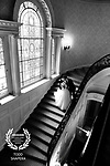 At Sleepy Hollow Country Club, a wedding couple enjoys their first look on the grand staircase by the stained glass window.