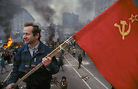 Moscow, Russia, 02/10/1993..An opposition demonstrator stands on a hijacked truck above burning barricades on the city's central ring road. Demonstrators built barricades in the city centre after riot police prevented them from marching to the Russian Parliament, which rebel Communist and nationalist deputies, led by Vice-President Alexander Rutskoi, had occupied after President Boris Yeltsin dissolved the parliament.