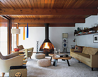 This living room is furnished with retro seating and a contemporary wood burner