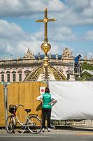 Eine Passantin betrachtet durch den Bauzaun die goldene Kuppel mit dem umstrittenen Kreuz vor der Montage auf dem wiedererbauten Berliner Stadtschloss (sog. Humboldt Forum).<br /> 28.5.2020, Berlin<br /> Copyright: Christian-Ditsch.de<br /> [NUR FUER REDAKTIONELLE ZWECKE! Werbung nur auf Anfrage beim Fotografen. Inhaltsveraendernde Manipulation des Fotos nur nach ausdruecklicher Genehmigung des Fotografen. Vereinbarungen ueber Abtretung von Persoenlichkeitsrechten/Model Release der abgebildeten Person/Personen liegen nicht vor. NO MODEL RELEASE! Don't publish without copyright Christian-Ditsch.de, Veroeffentlichung nur mit Fotografennennung, sowie gegen Honorar, MwSt. und Beleg. Konto: I N G - D i B a, IBAN DE58500105175400192269, BIC INGDDEFFXXX, Kontakt: post@christian-ditsch.de<br /> Bei der Bearbeitung der Dateiinformationen darf die Urheberkennzeichnung in den EXIF- und  IPTC-Daten nicht entfernt werden, diese sind in digitalen Medien nach §95c UrhG rechtlich geschuetzt. Der Urhebervermerk wird gemaess §13 UrhG verlangt.]