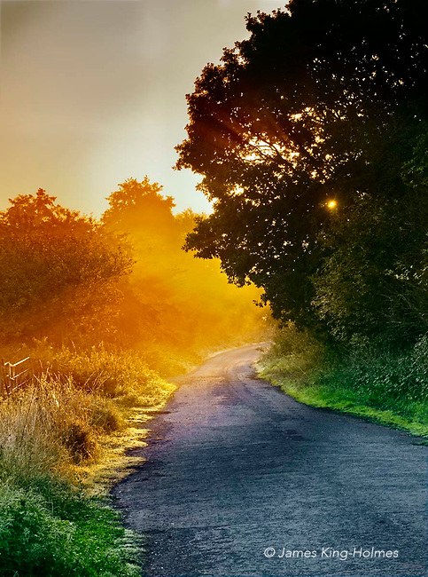 Sun rising over the abandoned main road in the village of Fyfield, Oxfordshire, UK. The trunk  road from Oxford to Swindon once ran through the village but a bypass was created in 197xx which cut off the village and the old road is now not used except for cyclists and pedestrians.