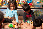 Preschool Headstart 3-5 year olds sand table group of girl and three boys playing in sand table separately horizontal
