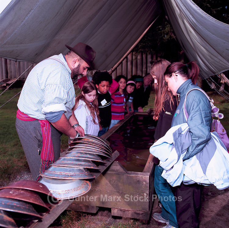 Fort Langley National Historic Site, BC, British Columbia, Canada - Re-enactor Miner showing Children how to pan for Gold.  Fort Langley was founded in 1827 as a Hudson's Bay Company Trading Post.