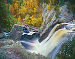 Tettegouche S.P., MN   <br /> Baptism River flowing over rock wall at High Falls with fall colored birch forest in the background