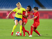 YOKOHAMA, JAPAN - AUGUST 6: Sofia Jakobsson #10 of Sweden is defended by Ashley Lawrence #10 of Canada during a game between Canada and Sweden at International Stadium Yokohama on August 6, 2021 in Yokohama, Japan.