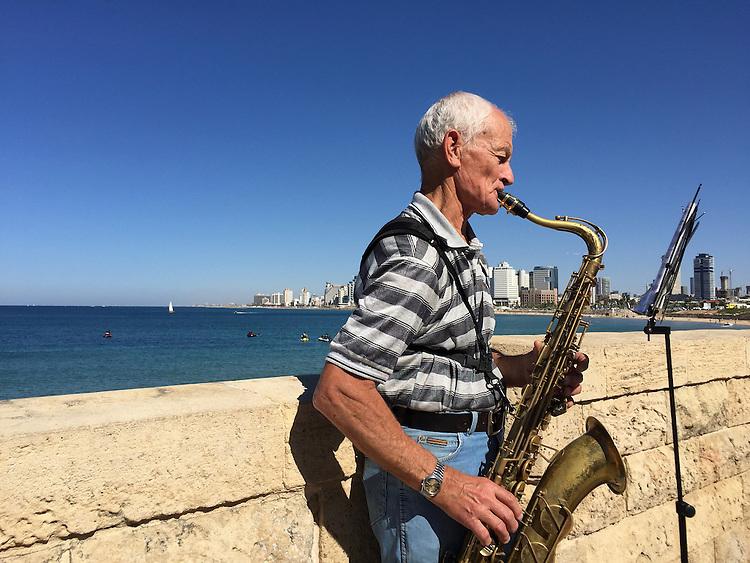 Musician plays sax in Jaffa, with Tel Aviv's modern skyline across the Mediterranean
