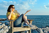 Woman enjoys the coastal view while speaking on a mobile phone.