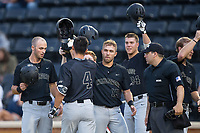 Stuart Fairchild (4) of the Wake Forest Demon Deacons is greeted at home plate by his teammates after hitting a grand slam against the West Virginia Mountaineers in Game Six of the Winston-Salem Regional in the 2017 College World Series at David F. Couch Ballpark on June 4, 2017 in Winston-Salem, North Carolina.  The Demon Deacons defeated the Mountaineers 12-8.  (Brian Westerholt/Four Seam Images)