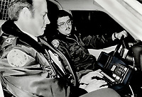 1985 FILE PHOTO - ARCHIVES -<br /> <br /> Computer cops: <br /> Toronto Metro police Constable Brian Hopkins; foreground; and his partner Constable Joe Doyle use the mobile display terminal (MDT) in their cruiser to check a car's licence number. The video screen is only about 11 by 8 centimetres (4 1/4 by 3 1/4 inches); but can display 300 characters in 10 lines of information. It is set on a post on the cruiser's floor.<br /> <br /> 1985<br /> <br /> PHOTO :  Erin Comb - Toronto Star Archives - AQP