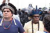 Indigenous leaders turn their backs to shock troops barring their way to the Riocentro United Nations conference during a demonstration by indigenous people, the Landless People's Movement (MST) and other civil society groups. The demonstrators are kept out of earshot and invisible to the UN conference. United Nations Conference on Sustainable Development (Rio+20), Rio de Janeiro, Brazil, 20th June 2012. Photo © Patrick Cunningham.