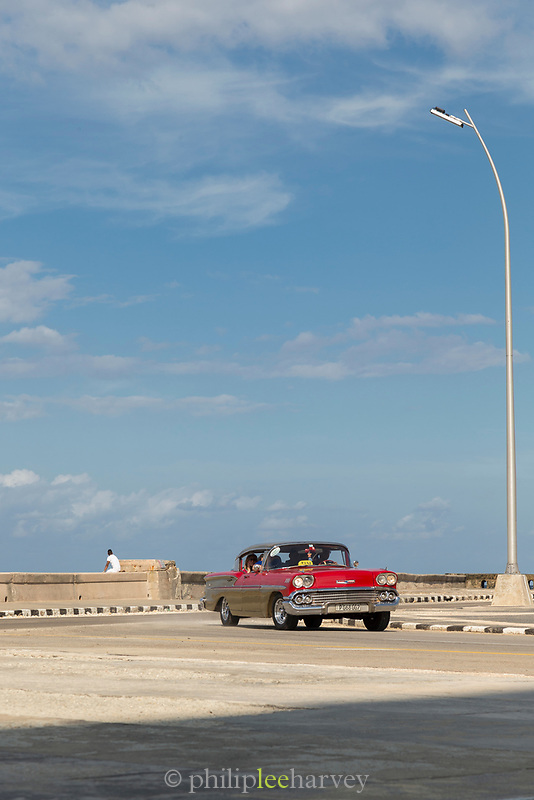 View of red vintage car under blue sky on Malecon road, Havana, Cuba