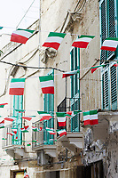 Italy, Apulia, Bari district, Monopoli, Italian flag bunting with a typical old building in the background